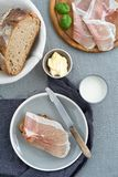 Parma ham on rustic bread. Parma ham on rustic sourdough bread with butter and milk stock image