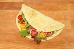 Parma ham and salad piada. On a wooden chopping board stock image