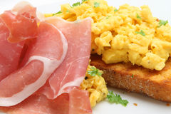 Parma Ham with Scrambled Eggs. Thinly sliced Parma ham with scrambled eggs and toast Royalty Free Stock Images