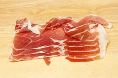 Parma ham on a board. Parma ham on a wooden chopping board stock images