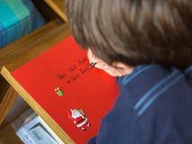 Parma, Italië - januari 2017: Jonge Jongen die op Rode Groetkaart schrijven Royalty-vrije Stock Afbeelding