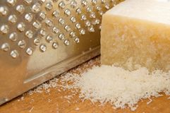 Parmesan. With grater on wood table royalty free stock photography
