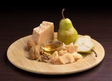 Parmesan avec du miel et des poires Photo stock