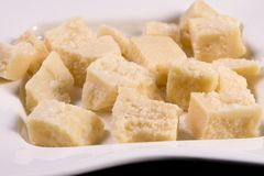 Parmesan Cheese. Pieces of Parmesan cheese in a white dish stock image