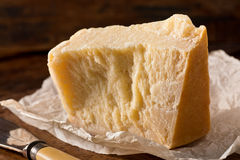 Parmesan Cheese. An aged authentic parmigiano reggiano parmesan cheese with wrapper and cheese knife Royalty Free Stock Images