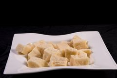 Parmesan Cheese Cubes. Pieces of Parmesan cheese in a white dish, on a black background stock photo