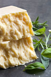 Parmesan Cheese. With fresh herbs over dark slate Royalty Free Stock Photography