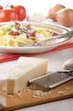 Parmesan cheese and grater on wood Royalty Free Stock Images