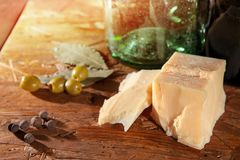 Parmesan and olives on wooden surface stock images