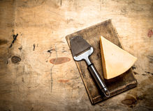 Parmesan cheese with knife on old cutting Board. Stock Photo