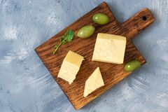 Parmesan cheese with olives on a cutting board, gray background, top view.