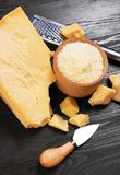 Parmesan cheese on wooden board. With grater and knife royalty free stock images