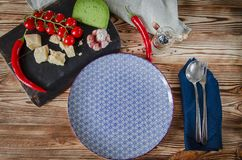 Parmesan, cherry tomatoes, chilli peppers, green cheese and garlic lie on a dark board that stands on a wooden table next to a royalty free stock image