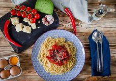 Parmesan, cherry tomatoes, chilli peppers, green cheese and garlic lie on a dark board that stands on a wooden table next to a stock photography