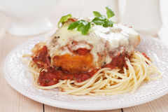 Parmesan chicken with spaghetti pasta. Parmesan chicken with melted cheese and tomato sauce served over spaghetti pasta Stock Photo
