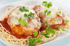 Parmesan chicken with spaghetti pasta. Parmesan chicken with melted cheese and tomato sauce served over spaghetti pasta Stock Image
