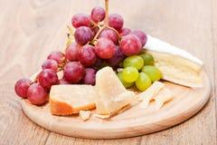 Parmesan et brie de fromage avec du raisin Photos stock