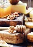 Parmesan, figues, écrous, miel et baguette - casse-croûte au blanc image stock