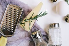 Parmesan hard cheese with rosemary, glass saltcellar and pepper, white chicken eggs and quail, grater and purple gauze fabric on a Royalty Free Stock Images
