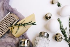 Parmesan hard cheese with rosemary, glass saltcellar and pepper, white chicken eggs and quail, grater and purple gauze fabric on a. Background Stock Image