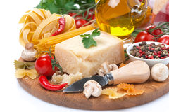 Parmesan, spices, olive oil, pasta and herbs on board, isolated Royalty Free Stock Photos