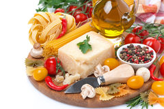 parmesan, spices, tomatoes, olive oil, pasta and herbs on board Stock Photography