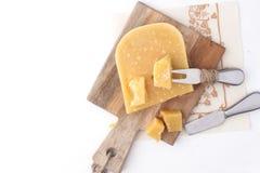 Parmesan, sur un conseil en bois et sur un fond blanc un couteau pour le fromage Nourriture traditionnelle L'espace libre pour le photo libre de droits