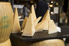 Parmesan is on table for sale on the market. Parmigiano-Reggiano is made from unpasteurized cow`s milk. Parmesan is on the table for sale on the market stock photos