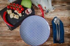 Parmesankäse, Kirschtomaten, Paprikapfeffer, grüner Käse und Knoblauchlüge auf einem dunklen Brett, das auf einem Holztisch nahe  lizenzfreies stockbild
