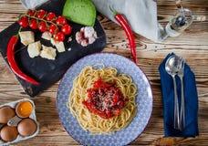 Parmesankäse, Kirschtomaten, Paprikapfeffer, grüner Käse und Knoblauchlüge auf einem dunklen Brett, das auf einem Holztisch nahe  stockfotografie