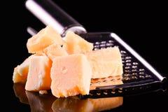 Parmesankäseparmesankäse und Reibe auf einer schwarzen glatten Tabelle mit Reflexion Parmesankäseparmesankäse lokalisiert auf sch Lizenzfreie Stockbilder