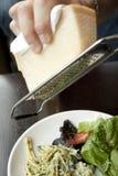 Parmesano que es afeitado en un rallador del queso en una determinación del café/de la tienda de delicatessen imagen de archivo