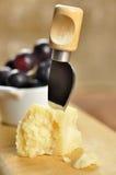 Parmesanost och druvor på en skärbräda Arkivfoton