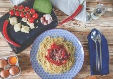 Parmezańscy, czereśniowi pomidory, chili pieprze, zielony ser i czosnku kłamstwo na zmrok desce która stoi na drewnianym stole ob zdjęcia stock