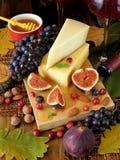 Parmezaanse kaas op een raad die door fig., druiven en honing wordt omringd royalty-vrije stock fotografie