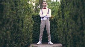 Parmi les buissons admirablement cultiv?s en parc, un jeune homme dans une chemise blanche, des pantalons, des bretelles ?l?gante banque de vidéos