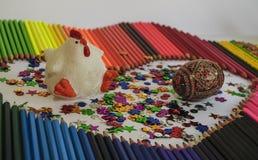 Parmi les crayons et le chiffre multicolores de sucrerie d'une poule blanche Image stock