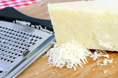 Parmigiana Cheese and Grater. A chunk of fresh parmigiana cheese next to a cheese grater with some grated cheese on the side Stock Photography