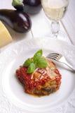 Parmigiana eggplant on dish. With glass of wine  traditional italian recipe Royalty Free Stock Photo