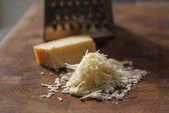 Parmigiano italiano grattato sul tagliere di legno con un blocco di parmasan e una grattugia nei precedenti Chiuda sulla foto fotografia stock libera da diritti