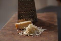 Parmigiano italiano grattato sul tagliere di legno con un blocco di parmasan e una grattugia nei precedenti Chiuda sulla foto immagine stock