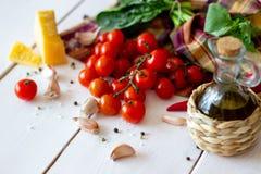 Parmigiano, pomodori, olio d'oliva ed altri ingredienti per il condimento dell'insalata Priorità bassa bianca fotografie stock libere da diritti