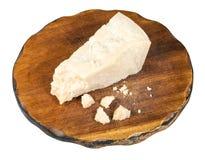 Parmigiano Reggiano cheese on dark board isolated. Piece of local italian Parmigiano Reggiano Parmesan hard cheese on dark wooden cutting board isolated on white royalty free stock photo