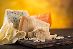 Parmigiano reggiano on wooden background Royalty Free Stock Images