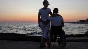 Parnärbilden som kramar afton, den rörelsehindrade personen och framtid fostrar att se in i avstånd arkivfilmer