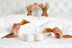 Parnederlag under duntäcket som tycker om frukosten i säng Arkivfoton