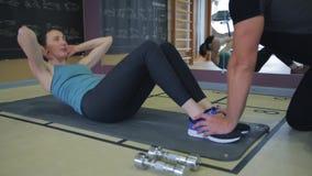 Parners da aptidão no sportswear que faz exercícios no gym Conceito do gym do esporte da aptidão Treinamento do Abs filme