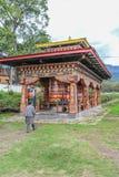 Paro Bhutan - September 17, 2016: Den bhutanesiska mannen som går till och med bönen, rullar in den Paro staden, Bhutan Royaltyfri Foto