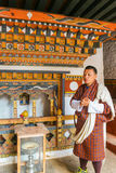 Paro, Bhutan - September 10, 2016: Local Bhutanese tourist guide wearing traditional clothing standing in a temple. Stock Photo