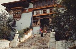 Paro Bhutan - September 10, 2016: Sikt för låg vinkel av turister som står på trappa för en gammal tempel Royaltyfri Foto